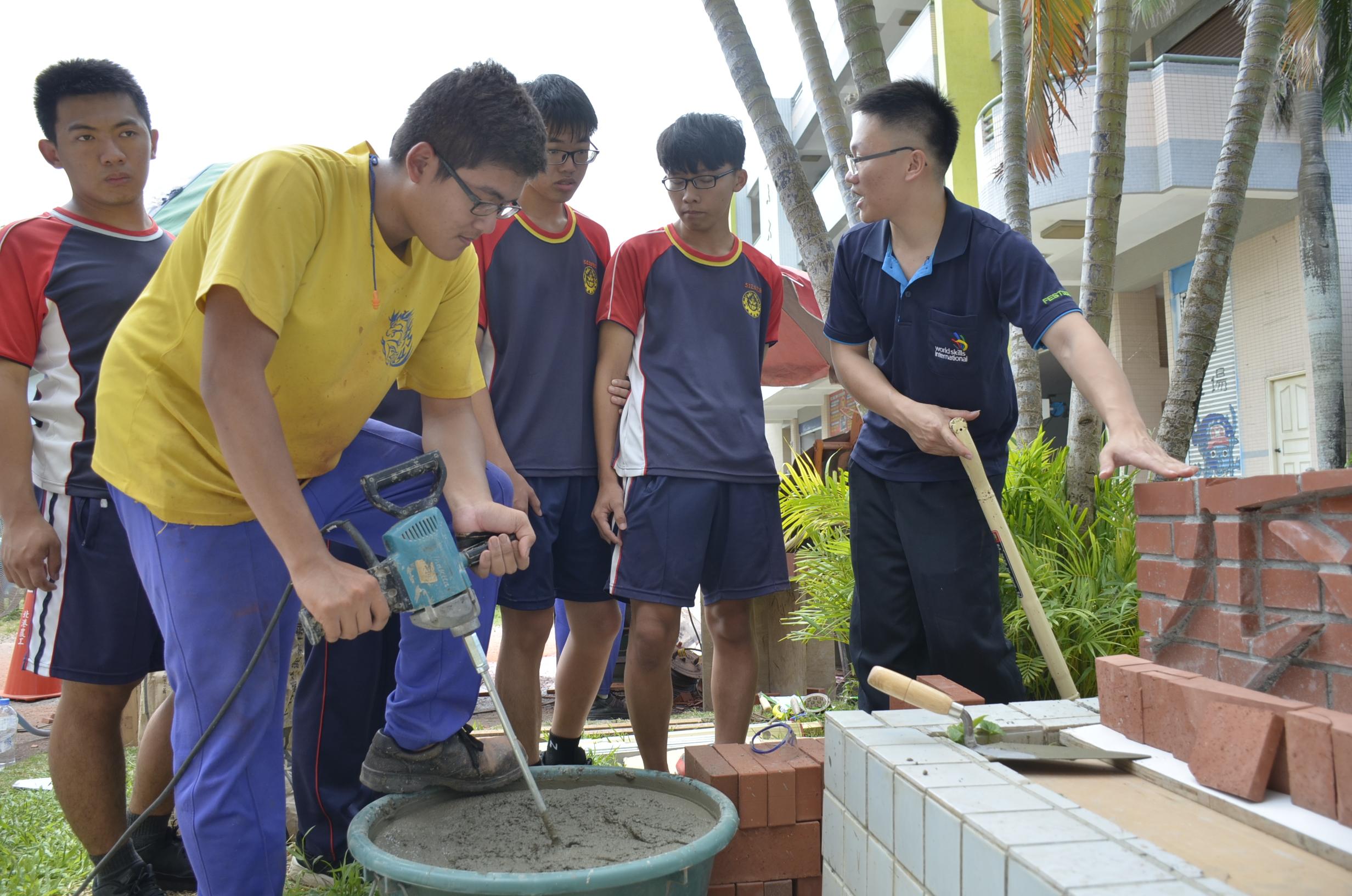▲砌磚國手周承誼為學生講解沙漿拌合技巧。