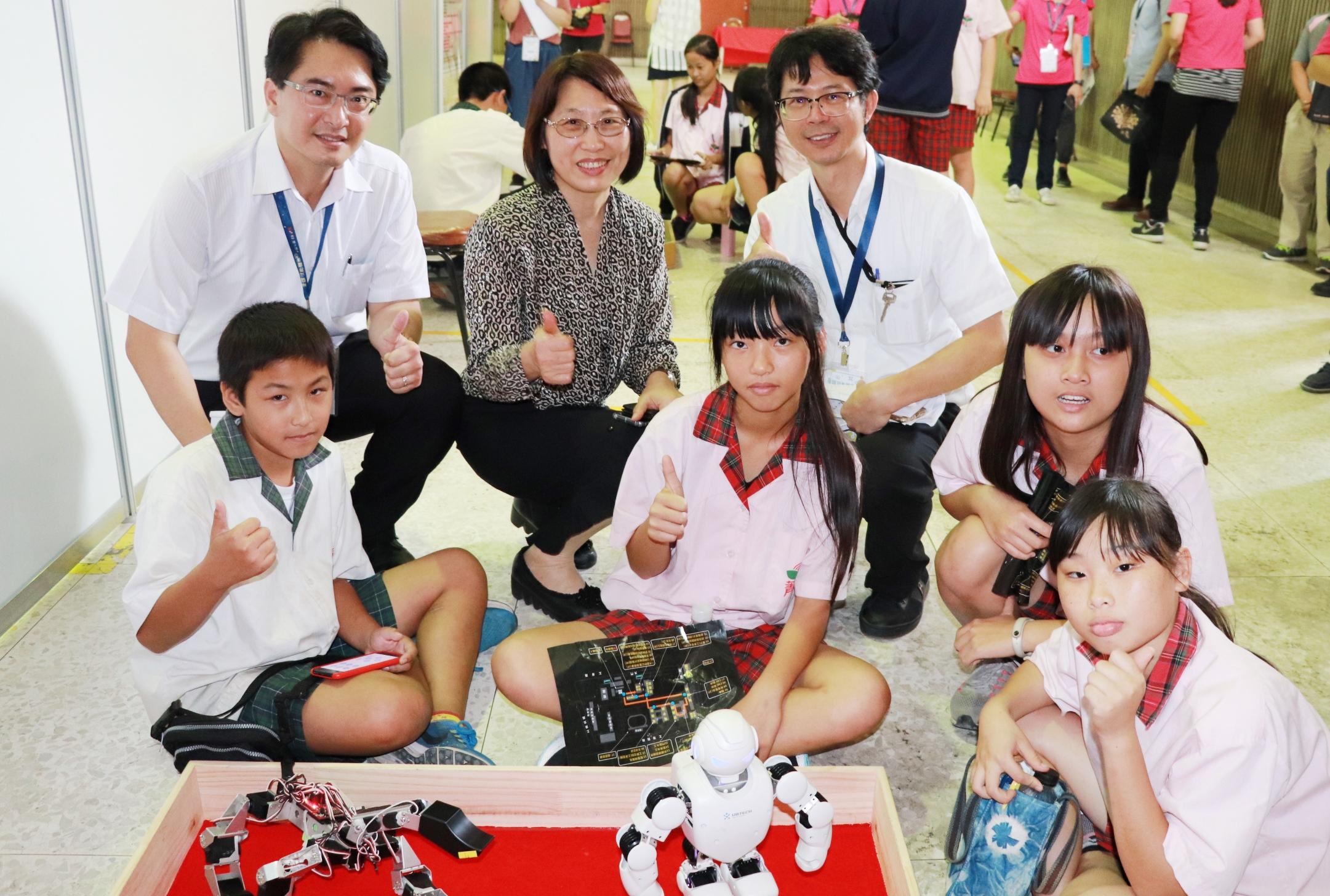 ▲國中生體驗機器人,發展署主任秘書王玉珊(後中)、雲嘉南分署長柯呈枋(後左)鼓勵青年學技能
