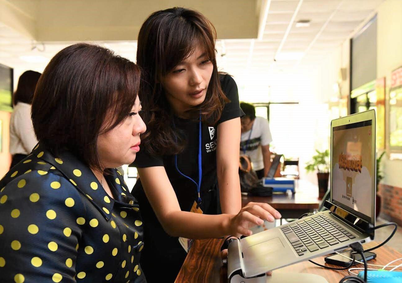 ▲科技輔具研發人員向勞動力發展署施貞仰副署長(左)介绍眼動控制系統的操作